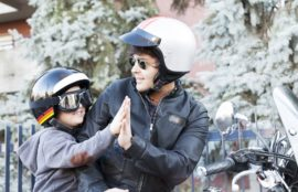 Father and son riding motorcycle wearing safety gears.